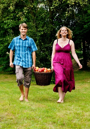 Couple (man and woman) carrying a basket with freshly harvested apples Stock Photo - 11912268