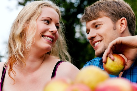 Couple (man and woman) eating freshly harvested apples - in front of them a basket with lots of fresh fruit photo