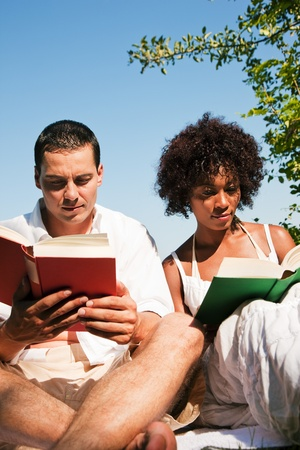 Couple reading books sitting outdoors in the sunshine in summer   photo