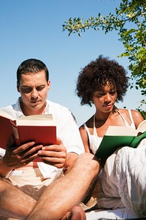 Paar B�cher lesen im Freien zu sitzen in der Sonne im Sommer