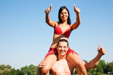 Couple in love - Woman in bikini sitting on her man�s shoulders under blue sky - summer and fun photo