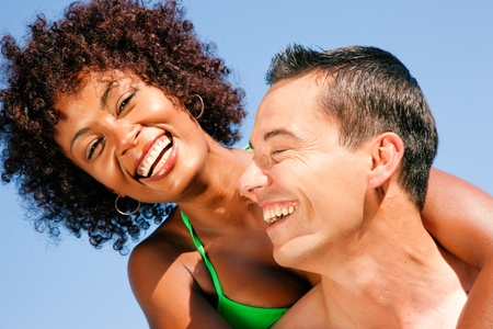 sportive: Couple in love - bikini-clad woman of color hugs a Caucasian man from behind under clear blue sky, both in beachwear in summer Stock Photo