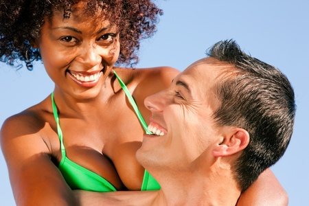 beachwear: Couple in love - bikini-clad woman of color hugs a Caucasian man from behind under clear blue sky, both in beachwear in summer Stock Photo
