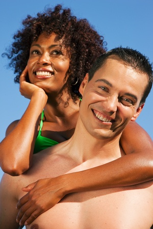 Couple in love - bikini-clad woman of color hugs a Caucasian man from behind under clear blue sky, both in beachwear in summer photo