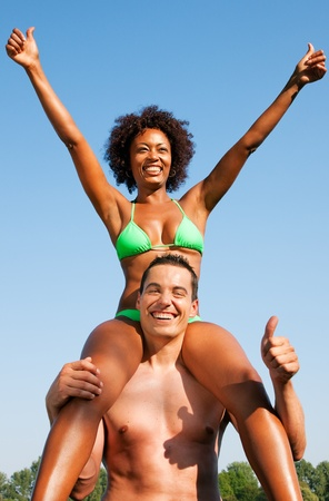 carrying girlfriend: Couple in love - Woman of color in bikini sitting on her man's shoulders under blue sky - summer and fun Stock Photo