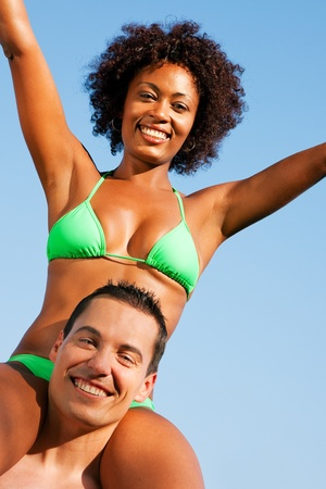 brazilian: Couple in love - Woman of color in bikini sitting on her man's shoulders under blue sky - summer and fun Stock Photo