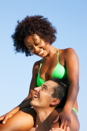 Couple in love - Woman of color in bikini sitting on her man�s shoulders under blue sky - summer and fun photo