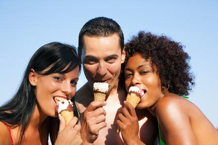 Gruppe von Freunden - ein Mann und zwei Frauen essen Eis in Badehose und Bikini, scheint es ein hei�er Sommertag sein