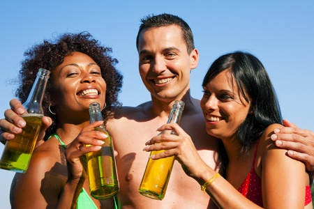 Group of friends - one man embraces two women and all have drinks in swimwear on the beach of a lake in summer photo