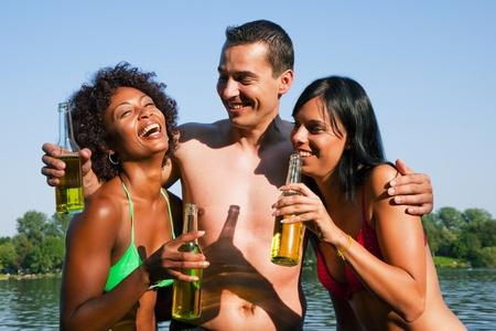 hombre tomando cerveza: Grupo de amigos - un hombre abraza a dos mujeres y todos tienen las bebidas en traje de ba�o en la playa de un lago en verano