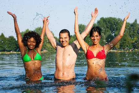Group of friends - man and to women stretching arms in the water of a lake on a hot summer day   photo