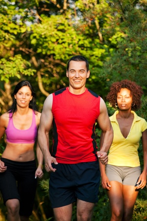 Group of friends exercising - man and two women jogging outdoors in beautiful evening light photo