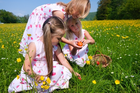 Children on an Easter Egg hunt on a meadow in spring photo