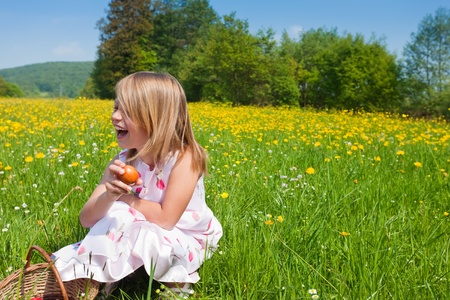 Child on an Easter Egg hunt on a meadow in spring