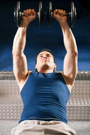 levantar pesas: Muy fuerte y apuesto hombre de levantamiento pesas (mancuernas) en un gimnasio