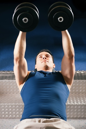 lifting weights: Muy fuerte y apuesto hombre de levantamiento pesas (mancuernas) en un gimnasio