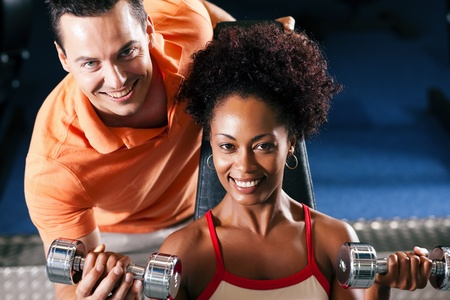 Woman with her personal fitness trainer in the gym exercising with dumbbells Stock Photo - 11912275