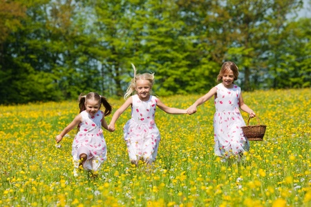 Children on an Easter Egg hunt on a meadow in spring still looking clueless photo
