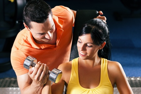 Woman with her personal fitness trainer in the gym exercising with dumbbells Stock Photo - 11897898