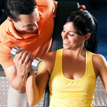 muskeltraining: Frau mit ihren pers�nlichen Fitness-Trainer im Fitnessstudio mit Hanteln Aus�bung