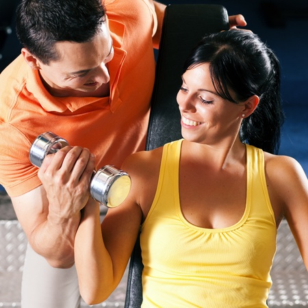 personal training: Woman with her personal fitness trainer in the gym exercising with dumbbells