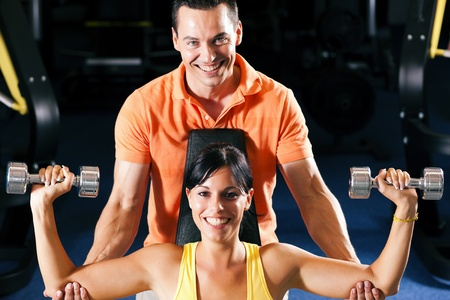 Woman with her personal fitness trainer in the gym exercising with dumbbells photo