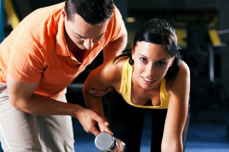 personal trainer woman: Woman with her personal fitness trainer in the gym exercising with dumbbells