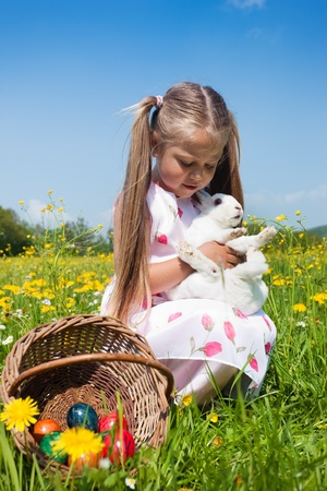 egg hunt: Little girl petting the Easter bunny on a meadow in spring