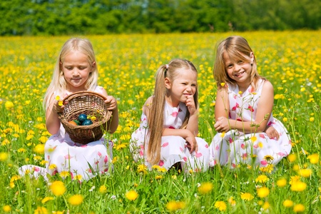 Children on an Easter Egg hunt on a meadow in spring Stock Photo - 11912635
