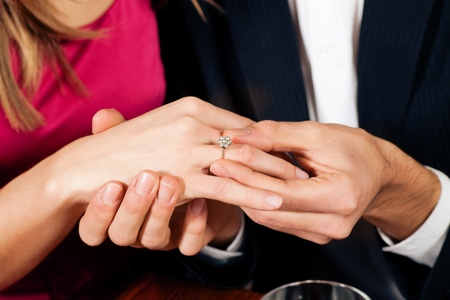 diamond ring: Man gently sticks a diamond ring on the finger of his fianc� after a romantic dinner (just hands to be seen)  Stock Photo