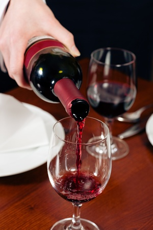 Waitress (just hands to be seen) refills the glass with red wine in a restaurant  photo