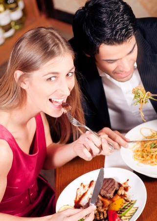 pareja comiendo: Pareja joven en el amor est� disfrutando de una cena rom�ntica, que tiene unos fideos, mientras que ella est� comiendo un buen filete