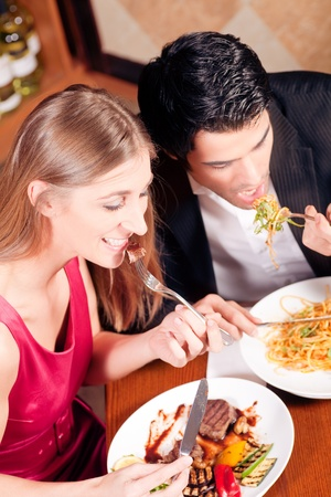 Young couple in love is enjoying a romantic dinner, he has some noodles while she is eating a good steak  photo