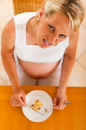 pregnant woman with a plate full of pills and capsules in front of her   photo