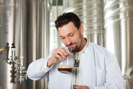 levadura: Brewer de pie en su fábrica de cerveza y está examinando la cerveza por su pureza