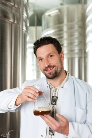 Brewer standing in his brewery and is examining the beer for its purity photo