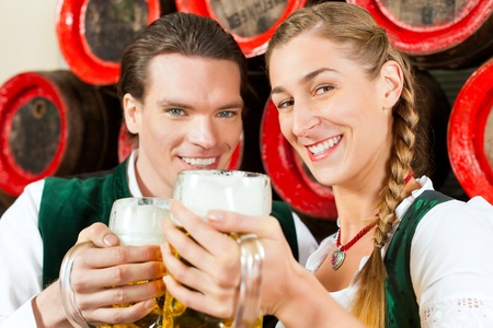 Young couple, man and woman, in traditional Bavarian Tracht drinking beer in a brewery in front of beer barrels photo