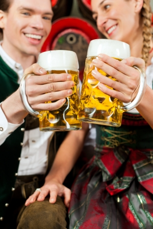 steins: Young couple, man and woman, in traditional Bavarian Tracht drinking beer in a brewery in front of beer barrels