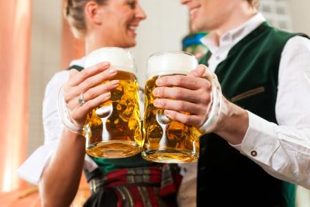 comida alemana: El hombre y la mujer con vasos de cerveza en Baviera Tracht en la cervecería frente a una caldera de cerveza