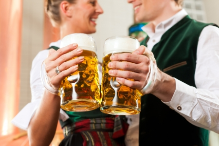 beer production: Man and woman with beer glasses in Bavarian tracht in brewery in front of a brew kettle