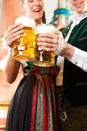 brew: Man and woman with beer glasses in Bavarian tracht in brewery in front of a brew kettle