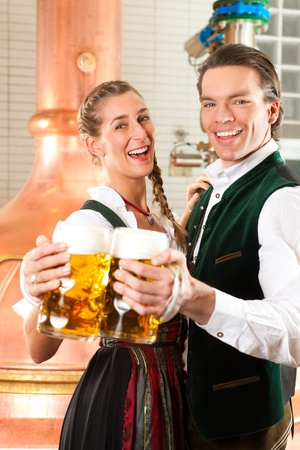 Man and woman with beer glasses in Bavarian tracht in brewery in front of a brew kettle Stock Photo - 11937365