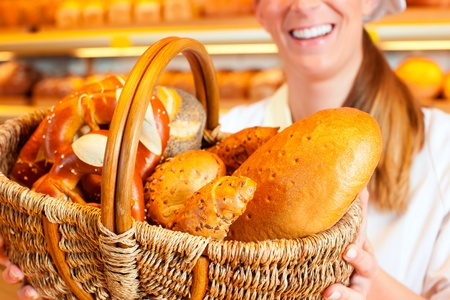 Female baker or saleswoman in her bakery selling fresh bread, pastries and bakery products in basket Stock Photo - 11937458