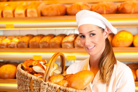 Female baker or saleswoman in her bakery selling fresh bread, pastries and bakery products in basket Stock Photo - 11937457