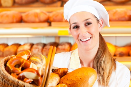 salesgirl: Female baker or saleswoman in her bakery selling fresh bread, pastries and bakery products in basket