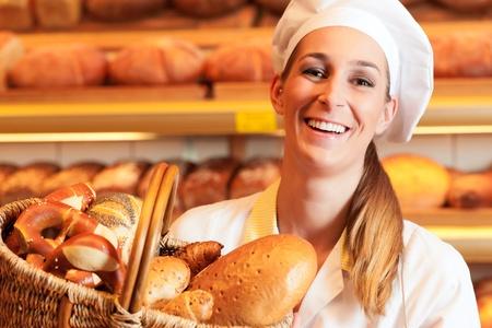 Kobieta piekarz lub sprzedawczyni w jej piekarni sprzedaje świeże pieczywo, ciastka, pieczywo w koszyku