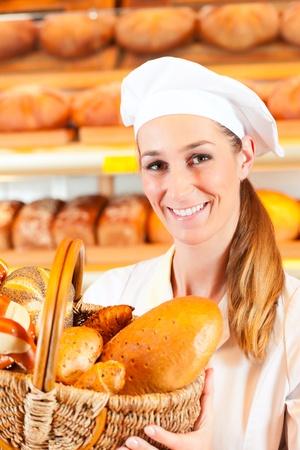 Weibliche B�cker oder Verk�uferin in ihrer B�ckerei verkaufen frisches Brot, Geb�ck und Backwaren im Korb