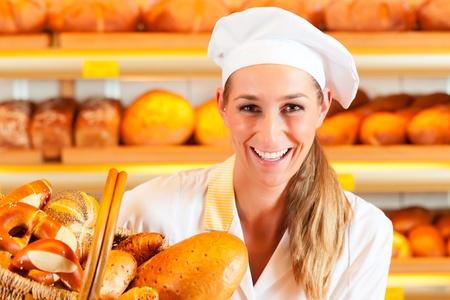 panettiere: Female panettiere o commessa nella sua panetteria vendere pane fresco, dolci e prodotti da forno nel carrello