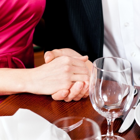 Couple, just hands to be seen, is holding hand while waiting for their food and drinks in a restaurant photo