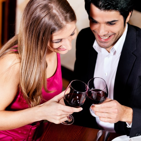 Junges Paar - Mann und Frau - in einem Restaurant klirren die Gl�ser Rotwein, auf den Gl�sern konzentrieren